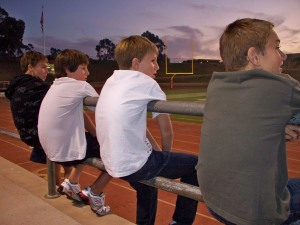 Teammates hanging out watching another pop warner team play